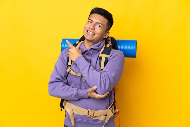 Hombre joven alpinista con una gran mochila aislado sobre fondo amarillo apuntando hacia el lado para presentar un producto