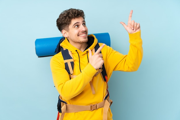 Hombre joven alpinista con una gran mochila apuntando con el dedo índice una gran idea