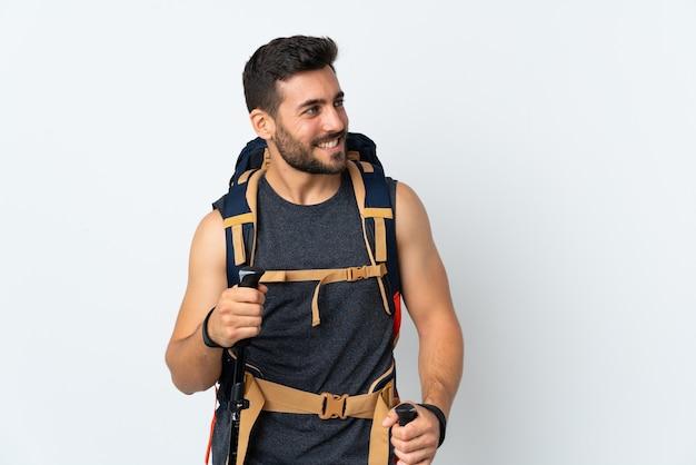 Hombre joven alpinista con una gran mochila y bastones de trekking aislado en blanco mirando hacia el lado