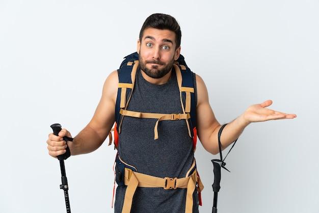 Hombre joven alpinista con una gran mochila y bastones de trekking aislados en blanco con dudas con expresión de la cara confusa