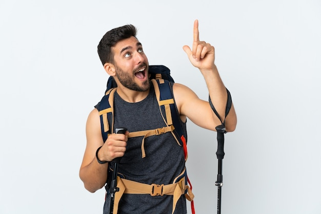 Hombre joven alpinista con una gran mochila y bastones de trekking aislados en blanco señalando con el dedo índice una gran idea