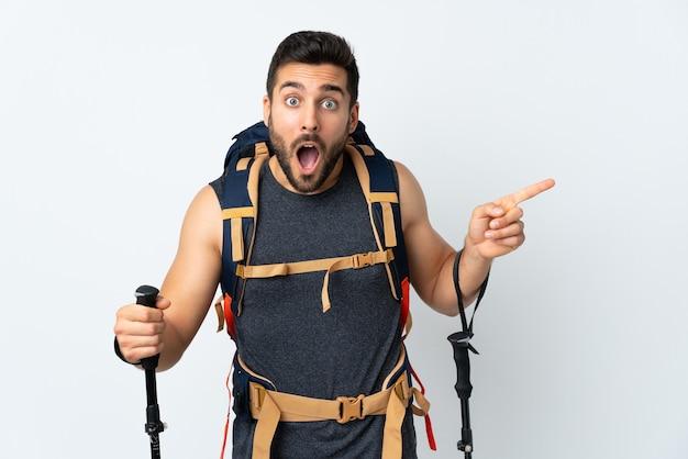 Hombre joven alpinista con una gran mochila y bastones de trekking aislados en blanco sorprendido y apuntando con el dedo hacia el lado