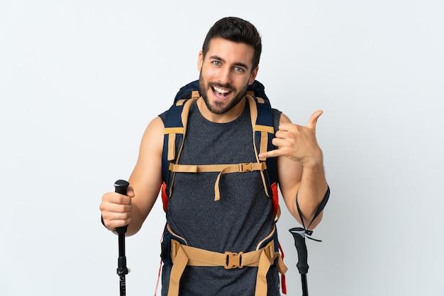 Hombre joven alpinista con una gran mochila y bastones de trekking aislados en la pared blanca haciendo gesto de teléfono