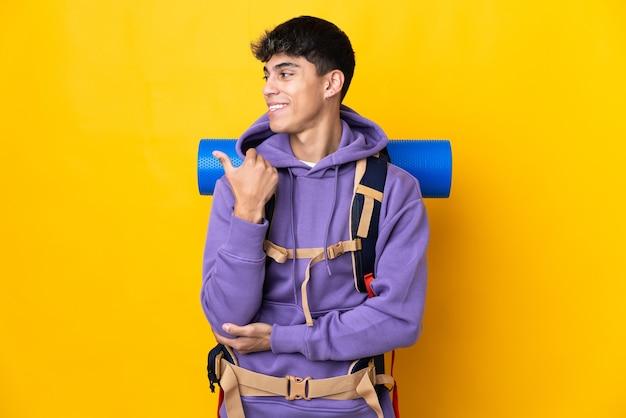 Hombre joven alpinista con una gran mochila sobre amarillo aislado apuntando hacia el lado para presentar un producto