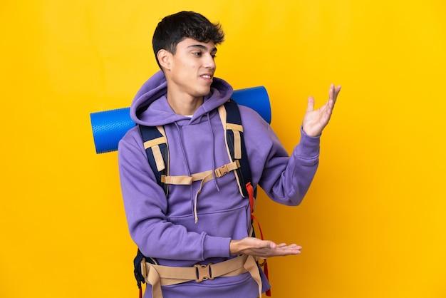 Hombre joven alpinista con una gran mochila sobre amarillo aislado extendiendo las manos hacia un lado para invitar a venir