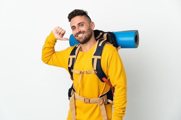 Hombre joven alpinista con una gran mochila sobre antecedentes aislados orgulloso y satisfecho de sí mismo