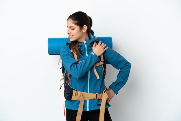 Hombre joven alpinista con una gran mochila sobre antecedentes aislados que sufren de dolor en el hombro por haber hecho un esfuerzo