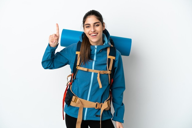 Hombre joven alpinista con una gran mochila sobre fondo aislado apuntando hacia una gran idea
