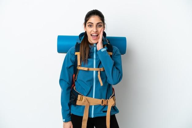 Hombre joven alpinista con una gran mochila sobre fondo aislado con sorpresa y expresión facial conmocionada