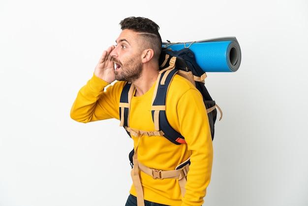 Hombre joven alpinista con una gran mochila sobre pared aislada gritando con la boca abierta hacia un lado