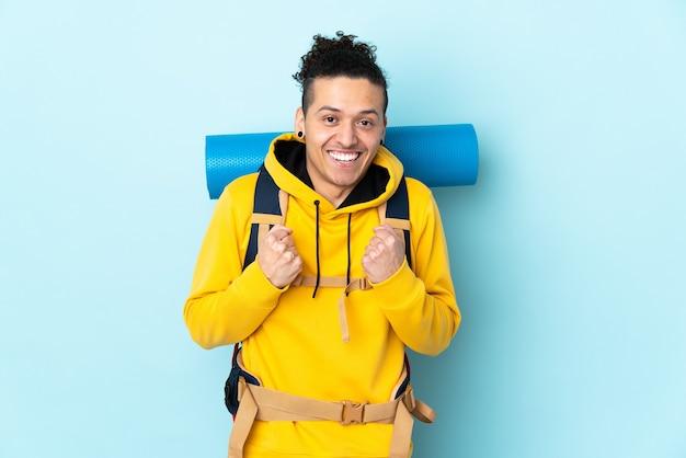 Hombre joven alpinista con una gran mochila sobre pared azul aislada celebrando una victoria