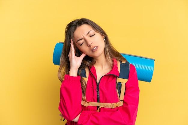 Hombre joven alpinista con una mochila grande aislado sobre fondo amarillo con dolor de cabeza