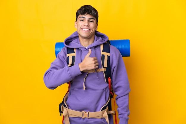 Hombre joven alpinista con una mochila grande sobre amarillo aislado dando un pulgar hacia arriba gesto