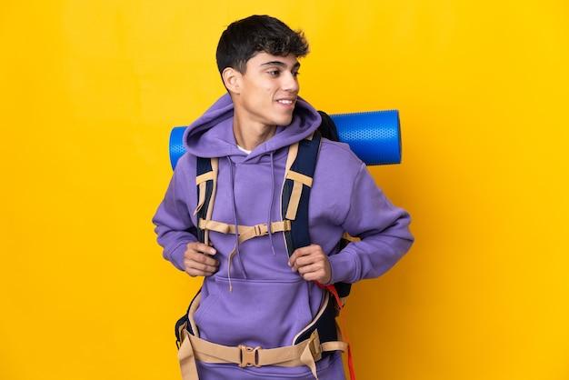 Hombre joven alpinista con una mochila grande sobre amarillo aislado mirando hacia un lado y sonriendo