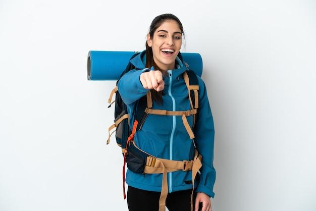 Hombre joven alpinista con una mochila grande sobre fondo aislado apuntando al frente con expresión feliz