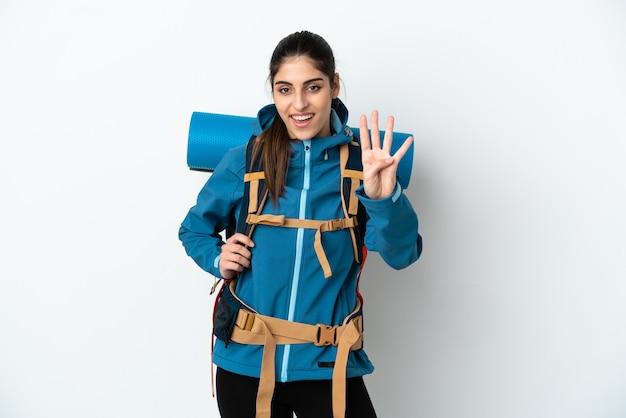Hombre joven alpinista con una mochila grande sobre fondo aislado feliz y contando cuatro con los dedos