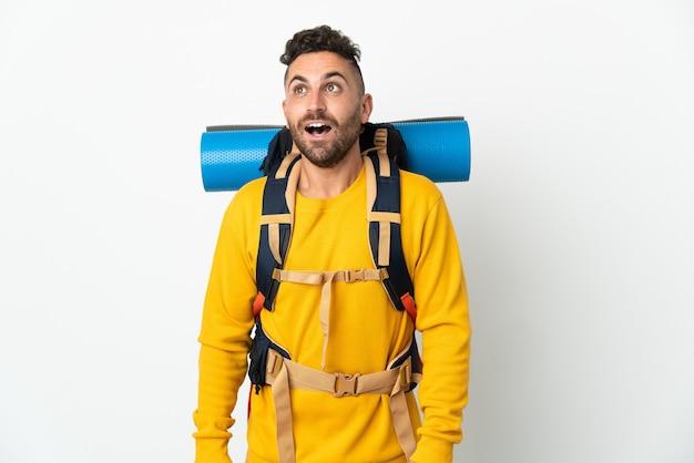 Hombre joven alpinista con una mochila grande sobre fondo aislado mirando hacia arriba y con expresión de sorpresa