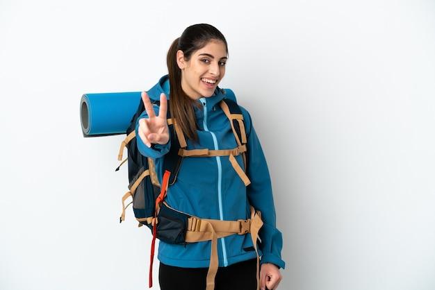 Hombre joven alpinista con una mochila grande sobre fondo aislado sonriendo y mostrando el signo de la victoria