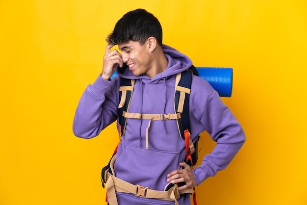 Hombre joven alpinista con una mochila grande sobre risa amarilla aislada