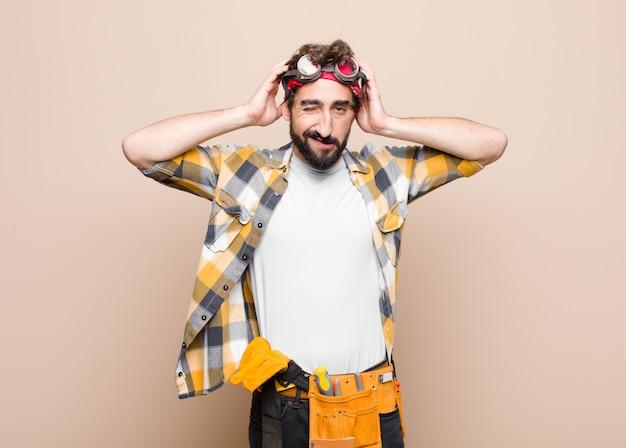 Hombre joven ama de llaves que se siente frustrado y molesto, enfermo y cansado del fracaso, harto de tareas aburridas y aburridas contra una pared plana