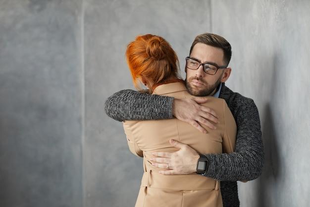 Hombre joven en anteojos abrazando a la mujer y apoyándola mientras están parados en la pared gris