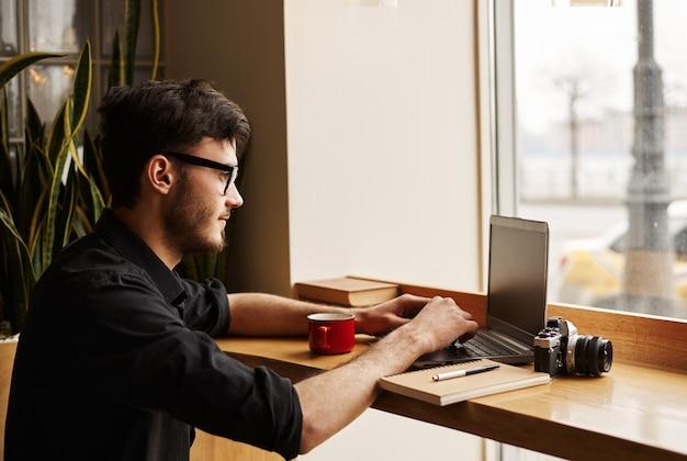 Hombre joven en anteojos busca ideas de cuidado de bebé en internet