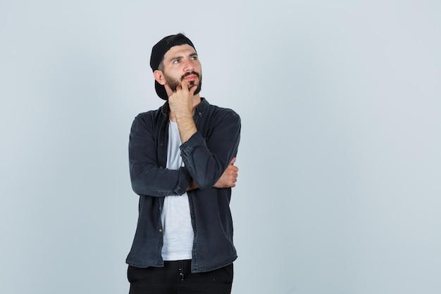 Hombre joven apoyando la barbilla en la mano