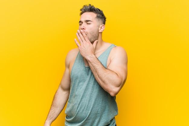 Hombre joven de la aptitud contra una pared amarilla que bosteza mostrando un gesto cansado que cubre la boca con la mano.