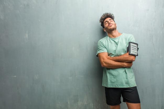 Hombre joven de la aptitud contra una pared del grunge orgulloso y confiado, señalando los dedos, ejemplo