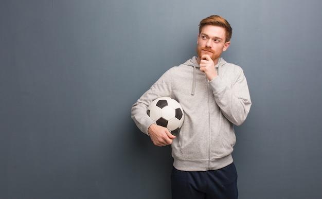 Hombre joven de la aptitud del pelirrojo que duda y confuso. él está sosteniendo una pelota de fútbol.