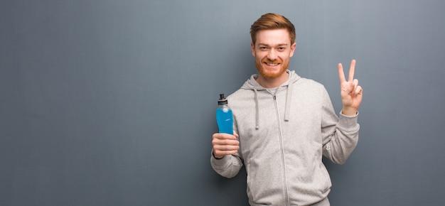 Hombre joven de la aptitud del pelirrojo que muestra el número dos. él está sosteniendo una bebida energética.
