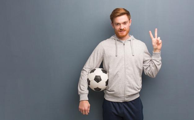 Hombre joven de la aptitud del pelirrojo que muestra el número dos. él está sosteniendo una pelota de fútbol.