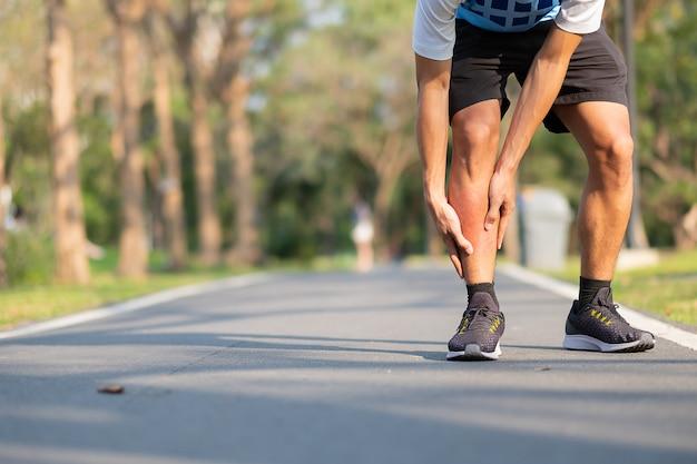 Hombre joven de la aptitud que lleva a cabo su lesión en la pierna de los deportes. dolor muscular durante el entrenamiento