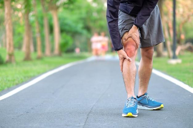 Hombre joven de la aptitud que lleva a cabo su lesión en la pierna de los deportes.