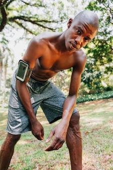 Un hombre joven apto africano con el brazalete en su mano que mira la cámara en el parque