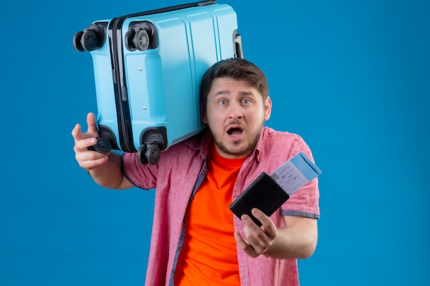 Hombre joven apuesto viajero molesto que sostiene la maleta y los billetes de avión que parecen confundidos muy emocionales y preocupados de pie sobre la pared azul
