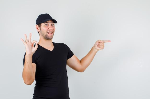 Hombre joven apuntando al lado con signo ok en camiseta negra