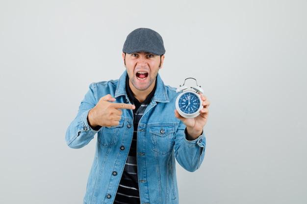 Hombre joven apuntando al reloj con chaqueta, gorra y mirando nervioso.