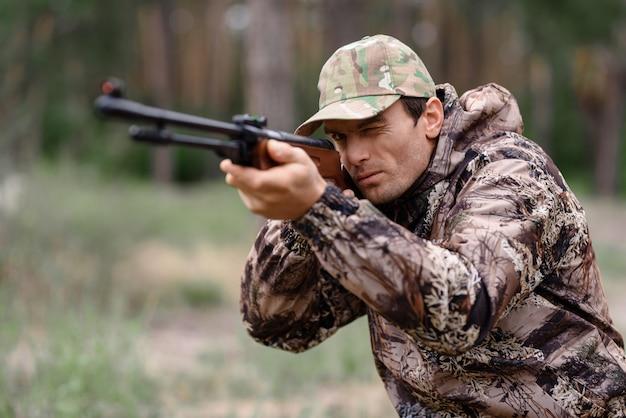 El hombre joven está apuntando con la caza del conejo de la escopeta.