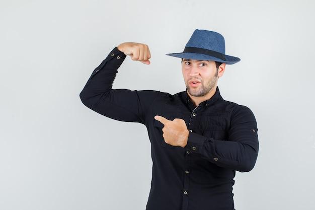 Hombre joven apuntando a su músculo con camisa negra, sombrero y luciendo fuerte.