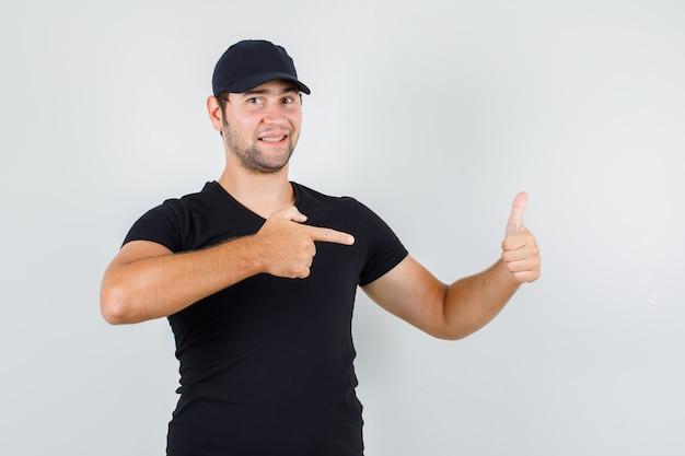 Hombre joven apuntando con su pulgar hacia arriba en camiseta negra, gorra y mirando alegre