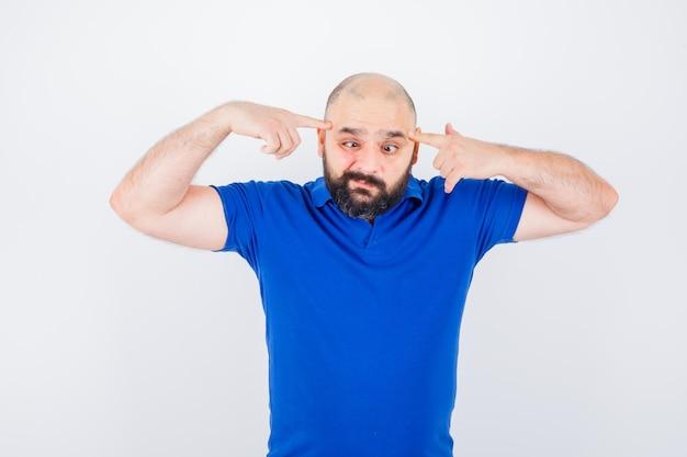 Hombre joven apuntando a sus ojos entrecerrados en camisa azul y mirando extraño. vista frontal.