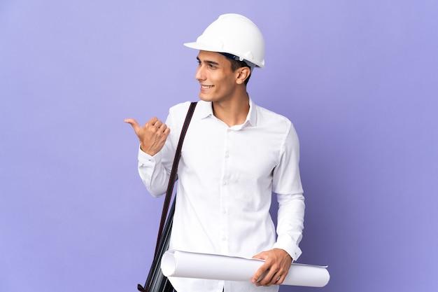 Hombre joven arquitecto aislado en la pared apuntando hacia el lado para presentar un producto