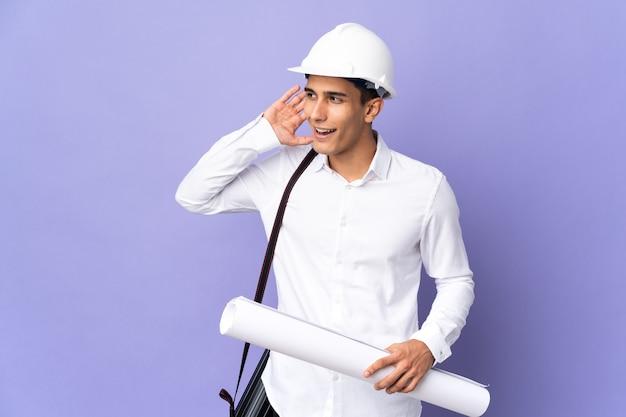 Hombre joven arquitecto aislado en la pared escuchando algo poniendo la mano en la oreja