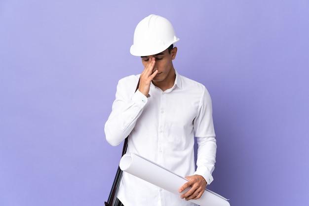 Hombre joven arquitecto aislado en la pared con expresión cansada y enferma