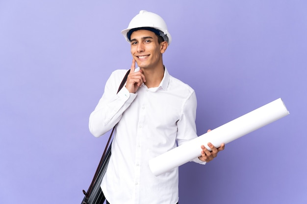 Hombre joven arquitecto aislado en la pared pensando en una idea mientras mira hacia arriba
