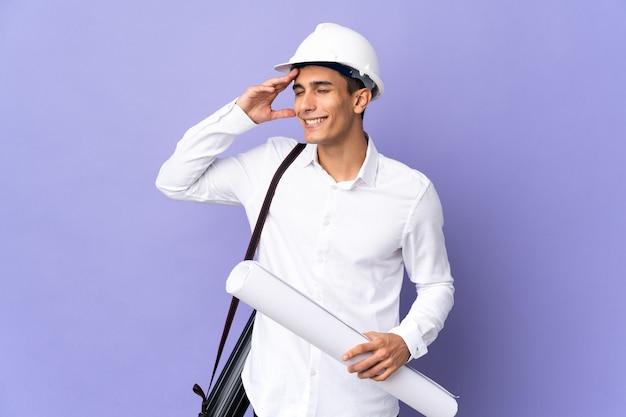 Hombre joven arquitecto aislado en la pared sonriendo mucho