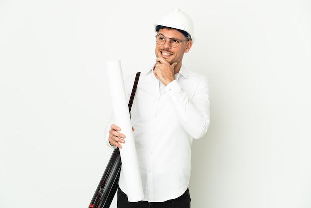 Hombre joven arquitecto con casco y sosteniendo planos aislado sobre fondo blanco mirando hacia el lado y sonriendo