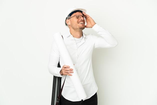 Hombre joven arquitecto con casco y sosteniendo planos aislado sobre fondo blanco sonriendo mucho