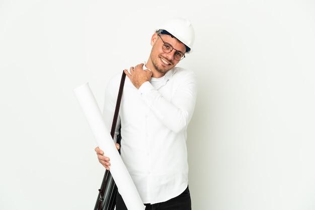 Hombre joven arquitecto con casco y sosteniendo planos aislados en blanco riendo
